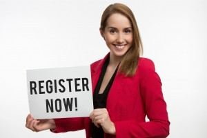 Woman in red blazer holding register now sign