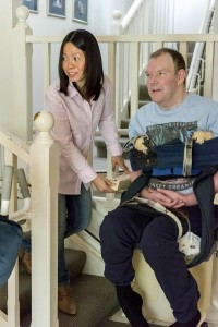 Man using stair lift with the help of his personal carer