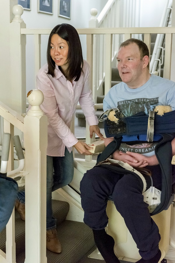 Man using stair lift with his personal care help
