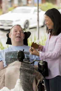 Man in wheel chair with his personal carer beside him